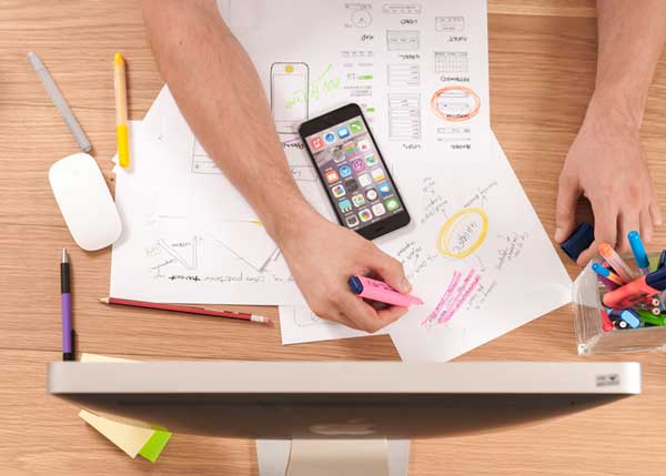 A user experience designer using a desktop on a wood table with pens, smartphone, and app wireframes